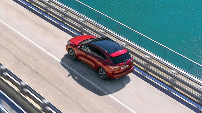 Red All-New Ford Kuga driving over bridge