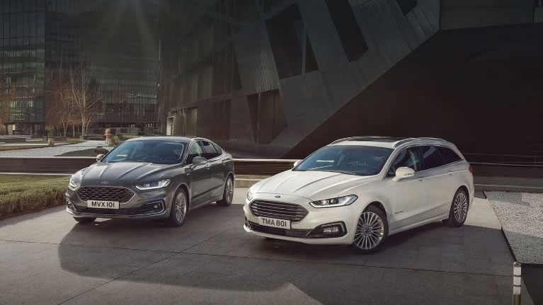 Dark and White Ford Mondeo parking in front of modern concrete building